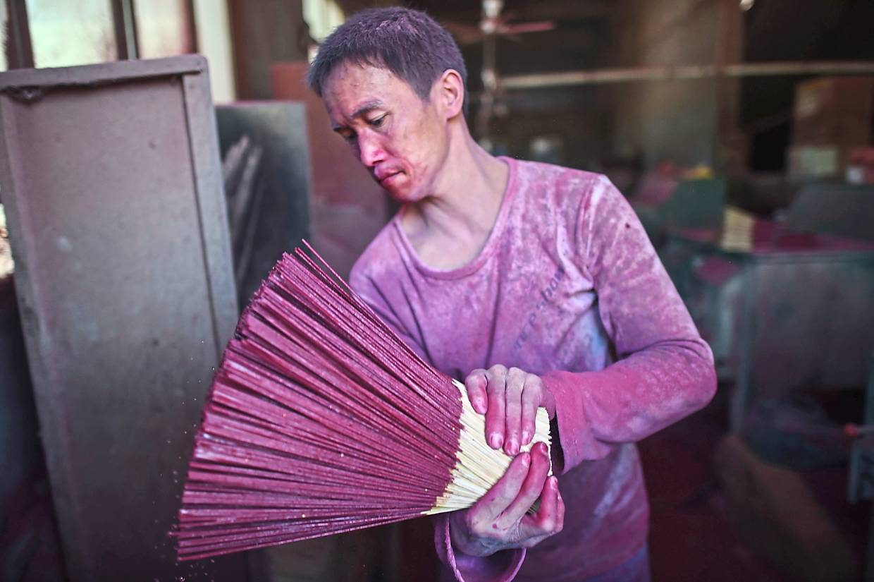 A worker covered with coloured powder as he makes incense sticks. Photo: AFP