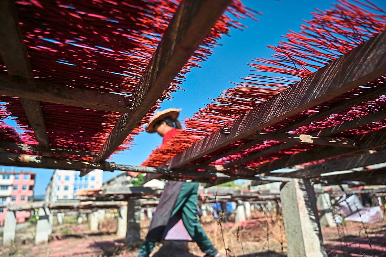 Incense sticks are placed on wooden platforms to dry at the Fujian Xingquan Incense Factory. Photo: AFP