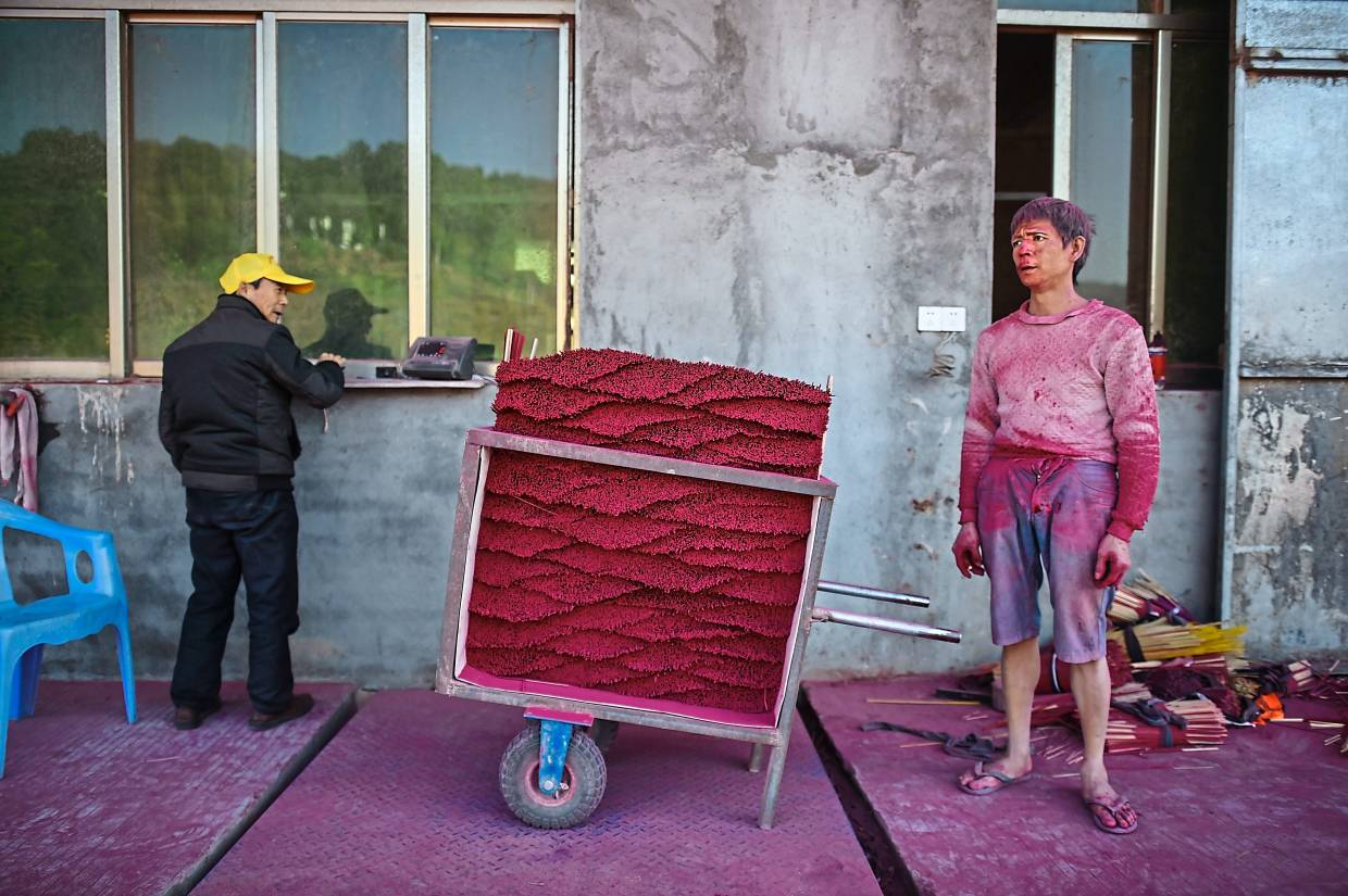 A worker (right) waiting to weigh the incense sticks he produced at factory. Photo: AFP