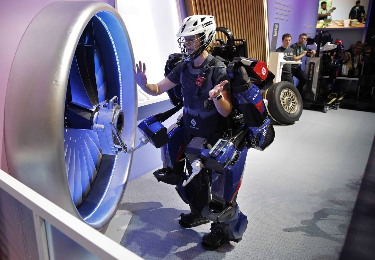 A woman demonstrating the Sarcos Robotics Guardian XO at the Delta Airlines booth at the 2020 CES tech show in Las Vegas. The full-body powered exoskeleton is designed to boost the user's strength and endurance. — AP