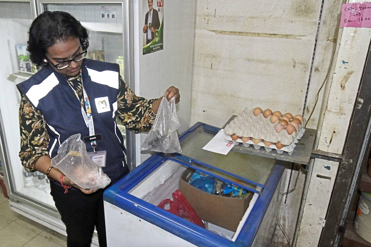 Bavani inspecting the food in a chiller box.