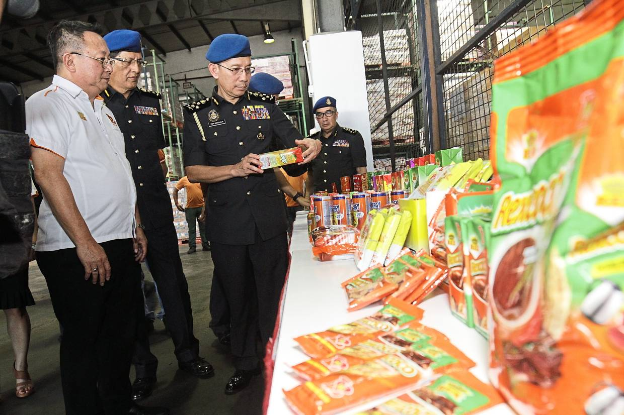 Iskandar (third left) taking a closer look at some products after launching 'Ops Catut 6.0' at REX Trading Sdn Bhd. Present is company chief executive officer Cheah Teng Lim (in white).