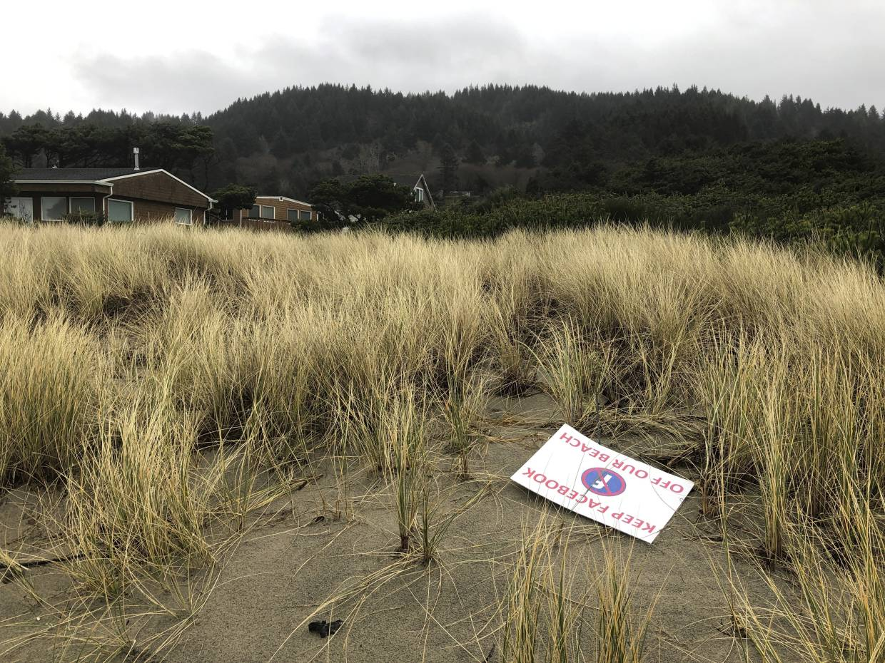 A sign denouncing Facebook's plans to put a landing site for a trans-Pacific fiber optic cable lies on the beachside property that a Facebook subsidiary bought in Tierra del Mar, Oregon.