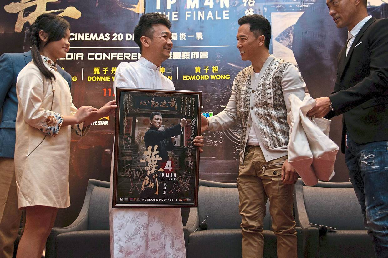 Bee (centre) and Xiang Zi (left) accepting an autographed movie poster of 'Ip Man 4' from actor Donnie Yen at a media conference to promote the movie in Kuala Lumpur last month. Photo: Lee Por Shiuan