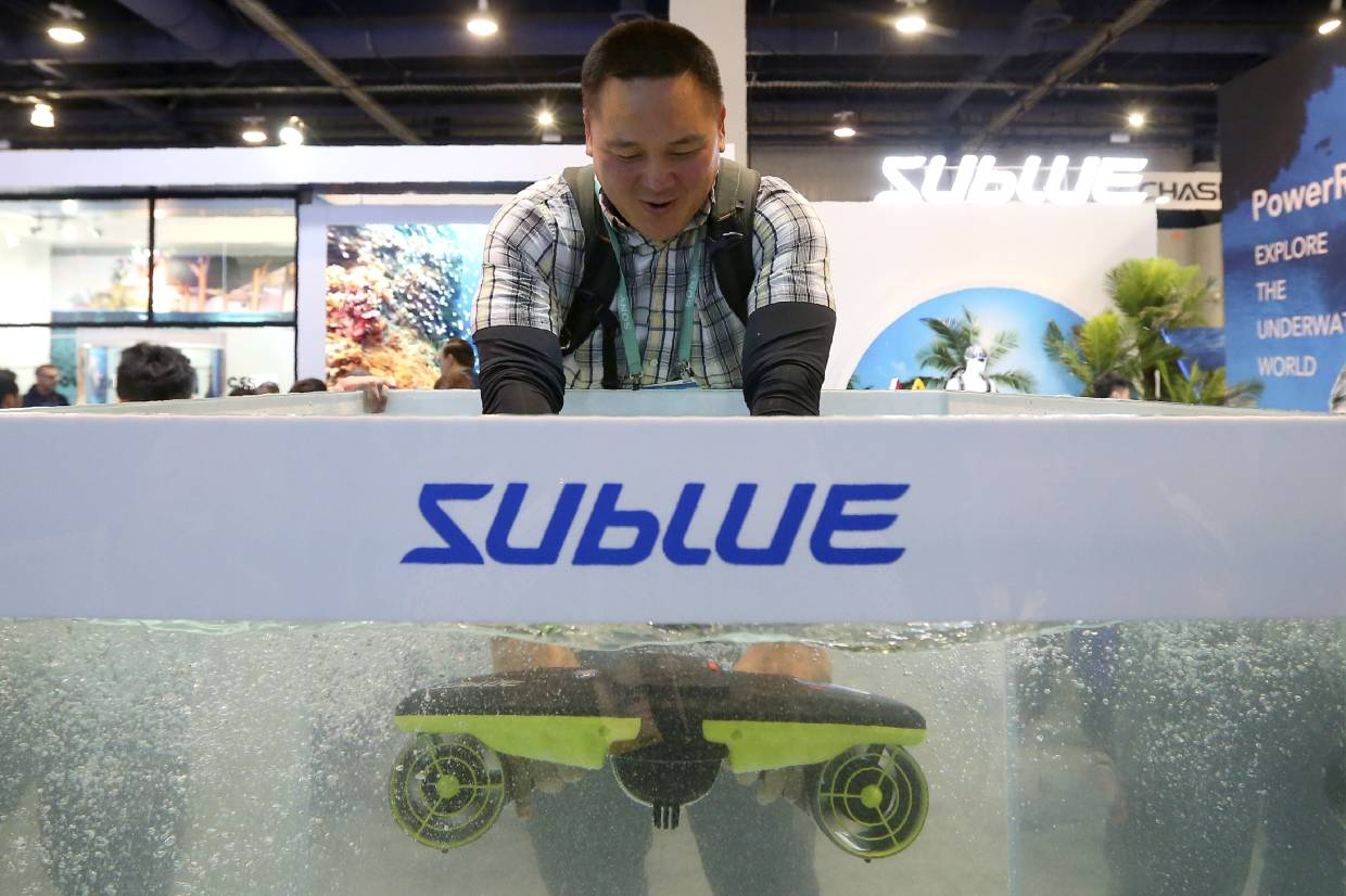 An attendee testing the Sublue Seabow in a water tank at the company's booth during the CES tech show in Las Vegas. — AP