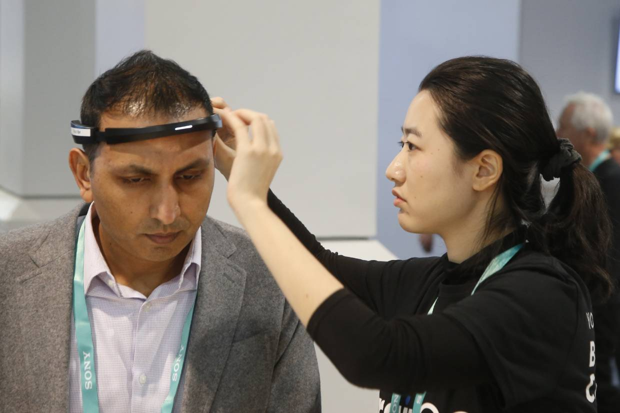 An Ampligence employee helping an attendee (left) with the BrainCo brainwave-sensing headband before linking with its software platforms, used for education, cognitive performance, and fitness spaces. — AP