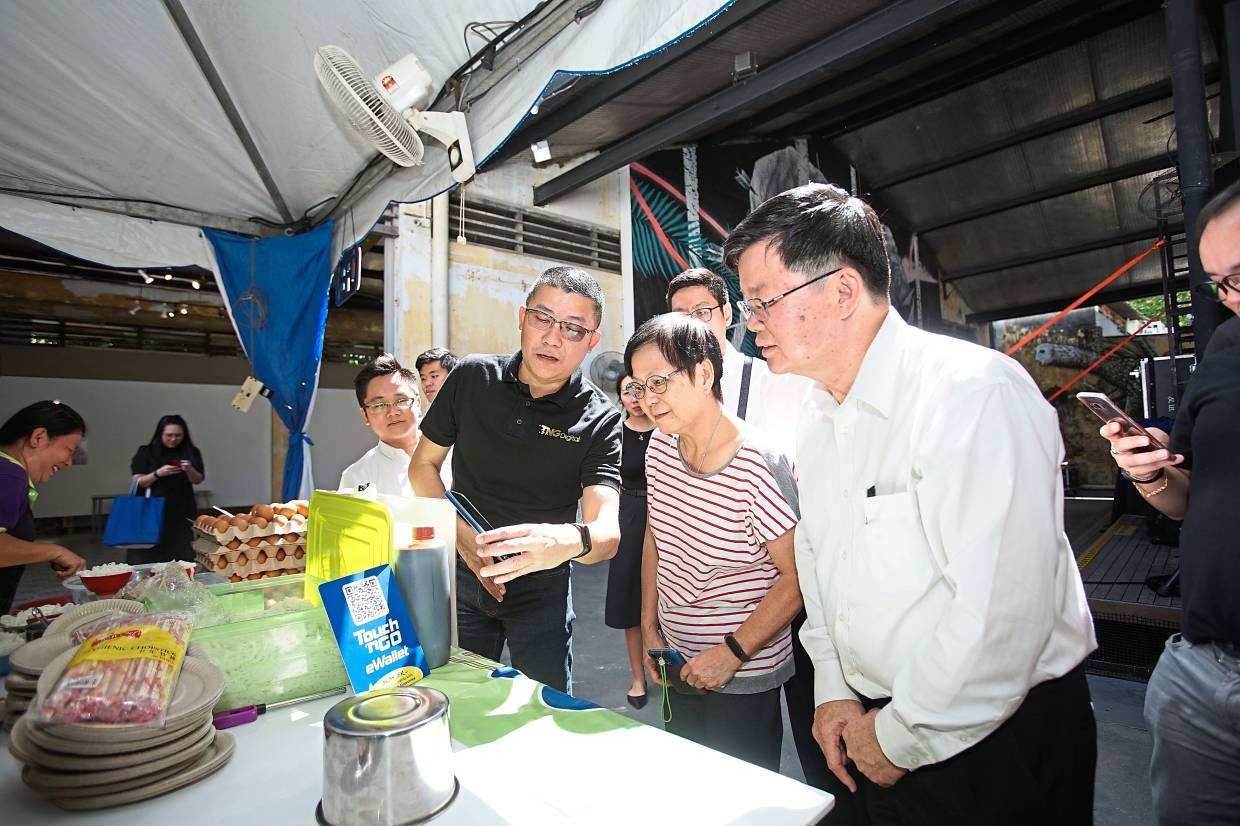 TNG Digital CEO Ignatius Ong (third from right) demonstrating how to use the e-wallet app at a food joint to a visitor and Penang chief minister Chow Kon Yeow (first from right). — Handout
