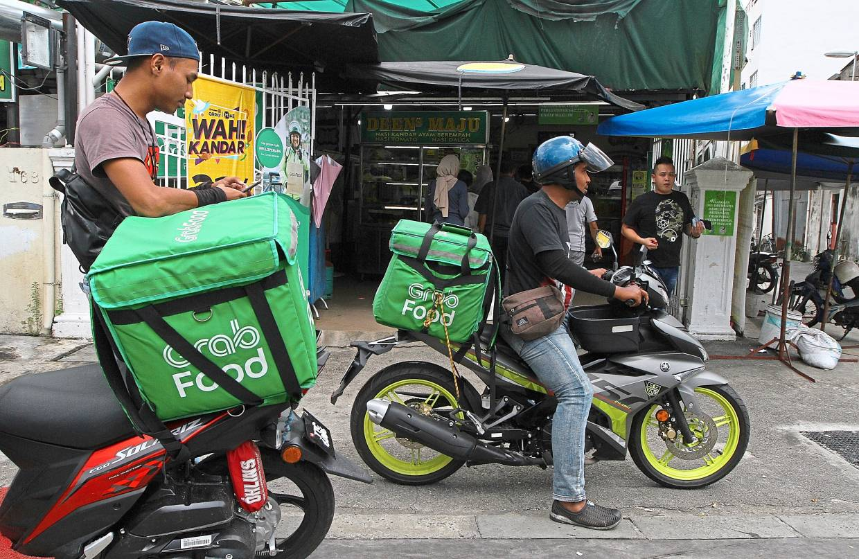 Food delivery: A file picture showing two Grab Food riders outside a nasi kandar restaurant in George Town.  From purely offering ride hailing services, Grab now also delivers food.