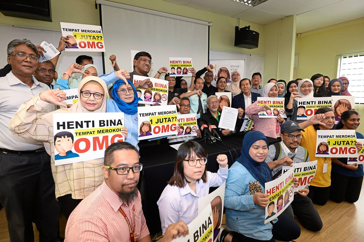 Thumbs down: Members from some of the 56 NGOs holding signs against the government's plan to allow designated smoking areas outside eateries and in public areas.