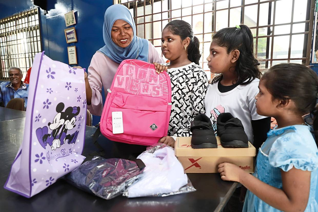 (From left) Ameeda with Nur Farzana and two other daughters checking out the items received from the Argyll Road KRT.