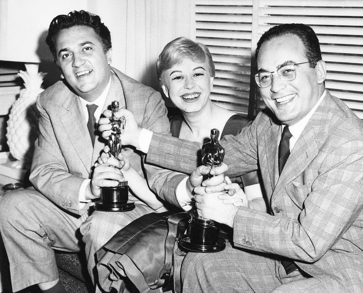 In this March, 1957 photo, Federico Fellini, left, his wife Giulietta Masina, and film producer Dino De Laurentiis hold the Oscars awarded for 'La Strada' in Los Angeles. Photo: Filepic