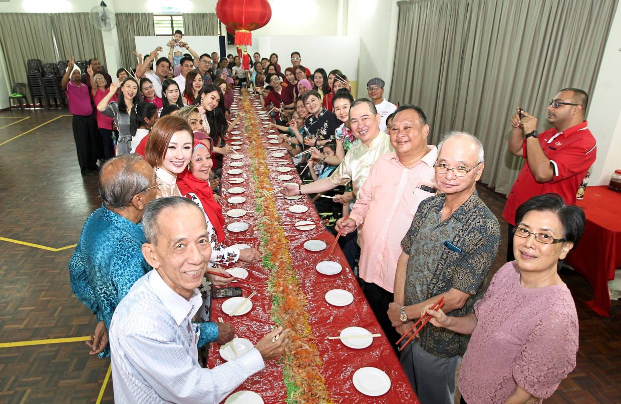 Ching (fourth from right) along with committee members of the association, sponsors, families and children taking part in a yee sang tossing session at the celebration.