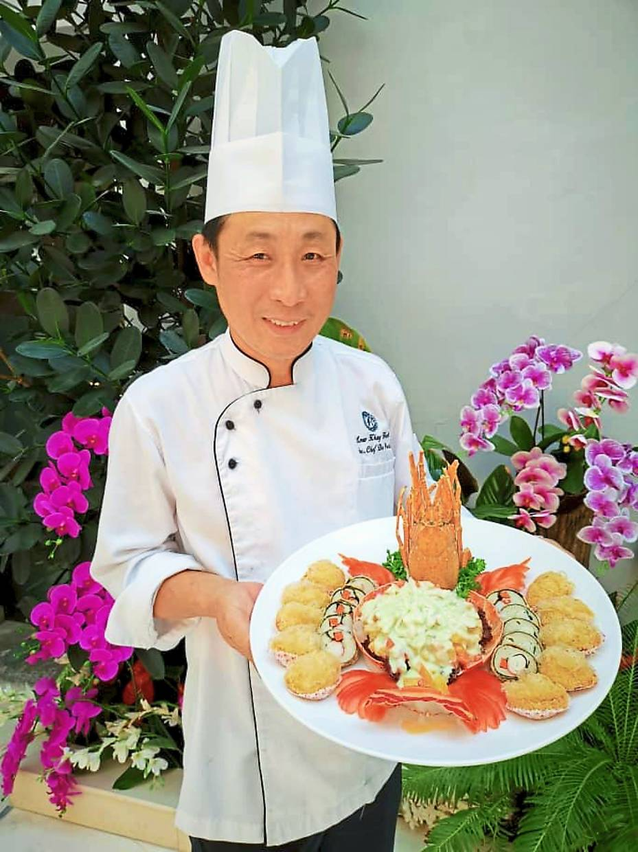 Royale Chulan Penang senior chef de partie showing the Lobster Prosperity Platter, one of the dishes featured in the Chinese New Year 8-Course Dinner Packages.