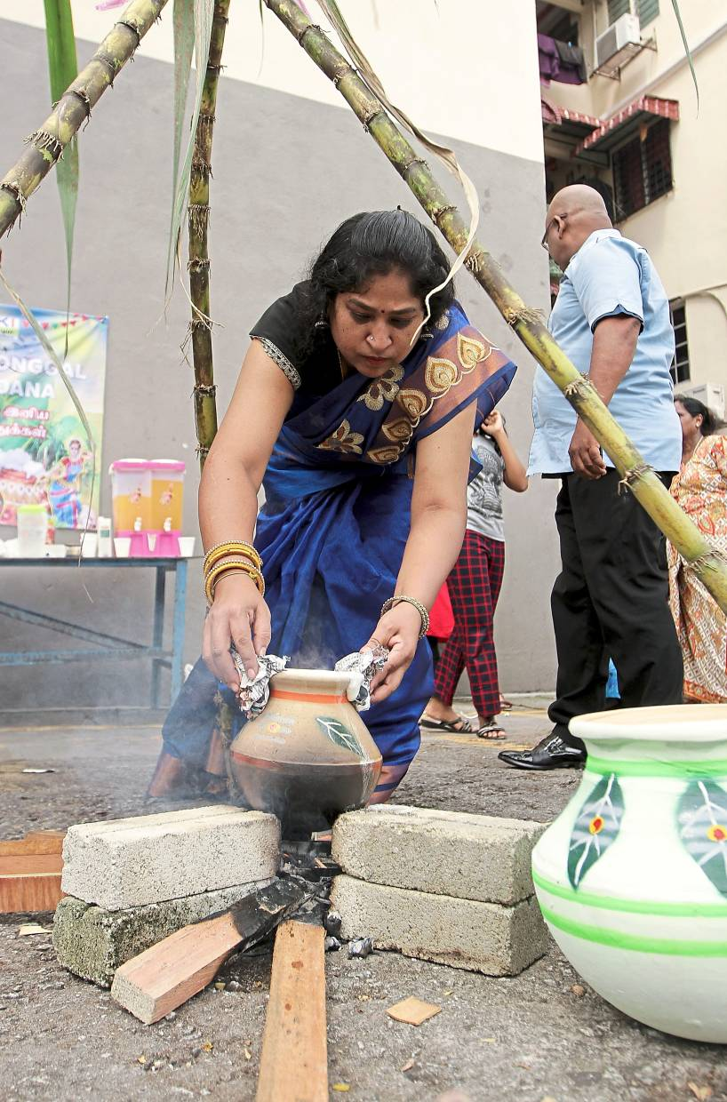 A woman removing the pot from the fire after cooking Ponggal rice.