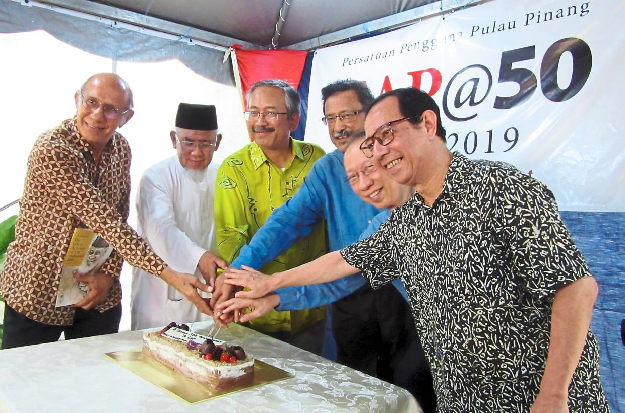 (From left) Anwar, National Consumers Advisory Council chairman Mohd Azmi Abdul Hamid, Rostam, Mohideen, Koh and Prof Dzulkifli cutting a cake to mark CAP's 50th anniversary