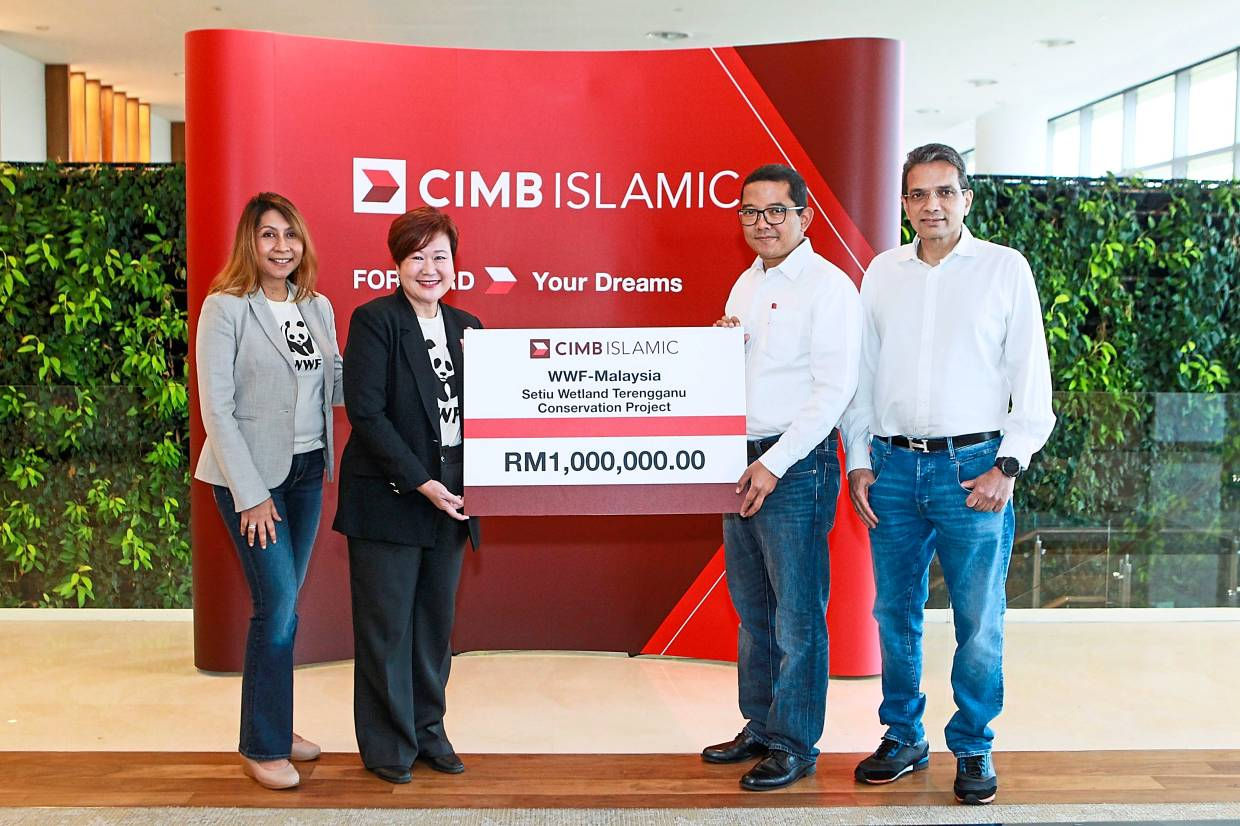 CIMB Islamic CEO Ahmad Shahriman Mohd Shariff (second right) with WWF-Malaysia CEO Sophia CK Lim (second left) accompanied by CIMB Group Consumer Banking CEO Samir Gupta and WWF-Malaysia director for marketing & communications Rozanna Basri at the mock cheque presentation for Setiu Wetlands Terengganu Conservation Project.