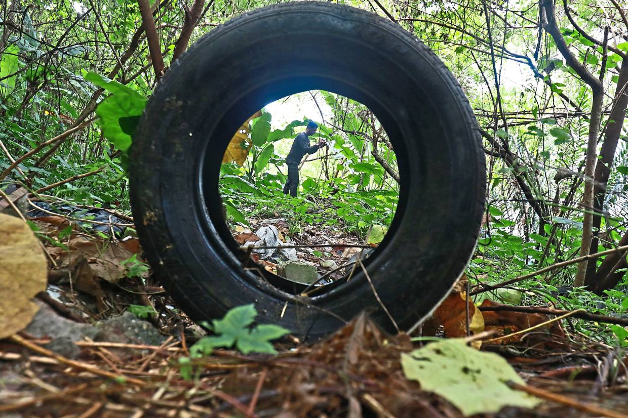 An enforcement officer getting photographic and video evidence of culprits dumping waste illegally in Kepong.