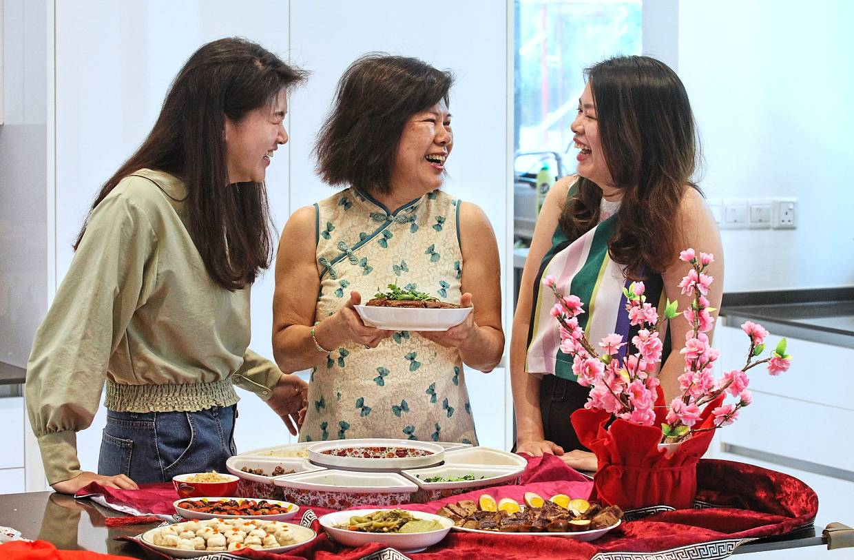 Tay (centre) says she has taught her daughters Sook Chuan (left) and Sook Fong how to cook all the family's heirloom recipes, so they typically help her prepare the CNY meals.