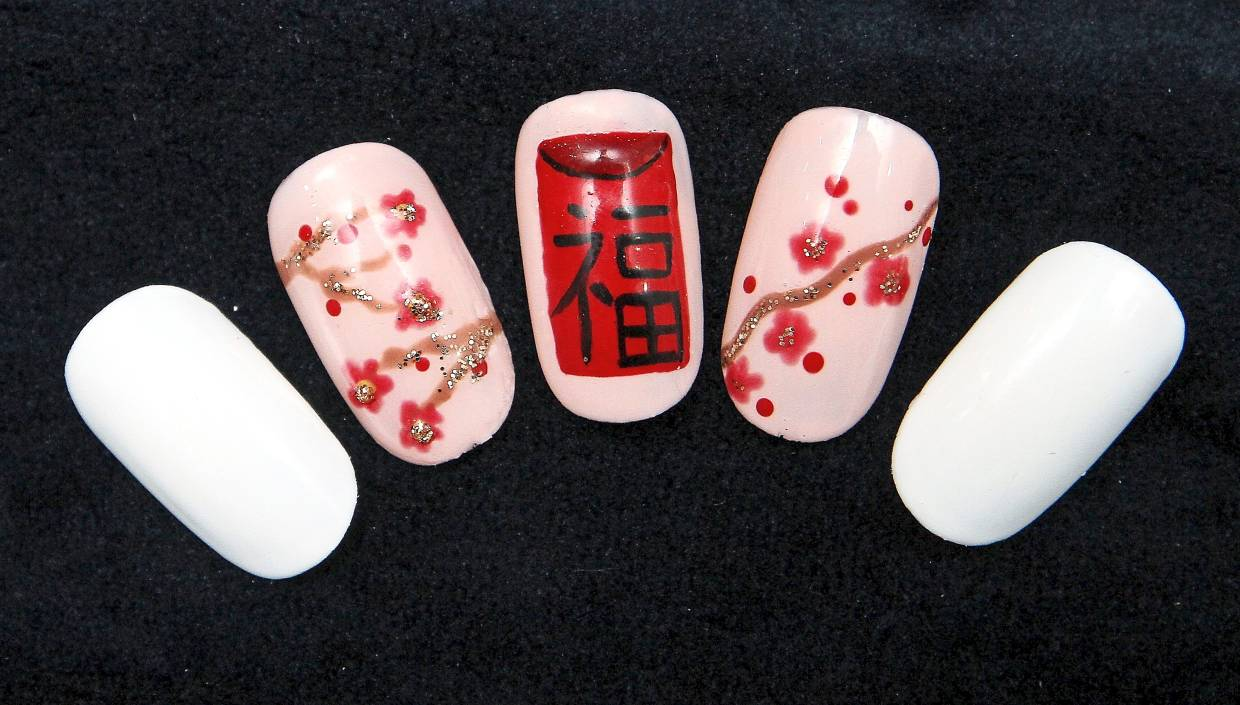 The red packet, a symbol of Chinese New Year, takes centrestage in this festive nail art by JJ Nail Studio. — AZLINA ABDULLAH/The Star