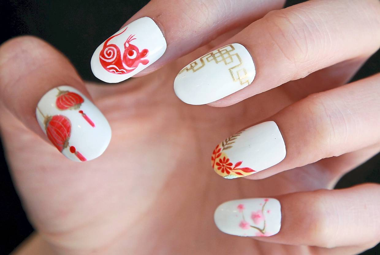 Nail artist Miko Tan incorporates the element of traditional paper cutting art with Chinese New Year elements, while highlighting a red rat. — NORAFIFI EHSAN/The Star