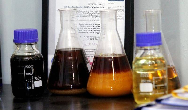 Pictured here are waste oils in lab flasks with their derivatives, encased in bottles.