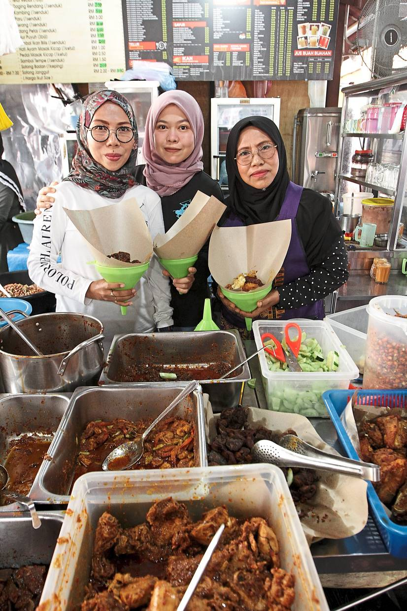 Nasi Lemak Tawaf founder Zulmah (right) with her daughters Dzuliya Dzulkifli (left) and Surida. Both now help Zulmah at the eatery.