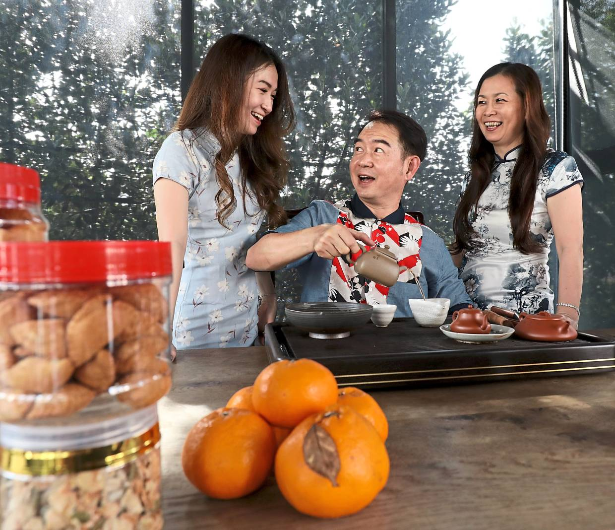 Seah (centre) making tea for the family while his wife Ng Kwai Wan, 54(right) and daughter Jeslyn, 25, look on.