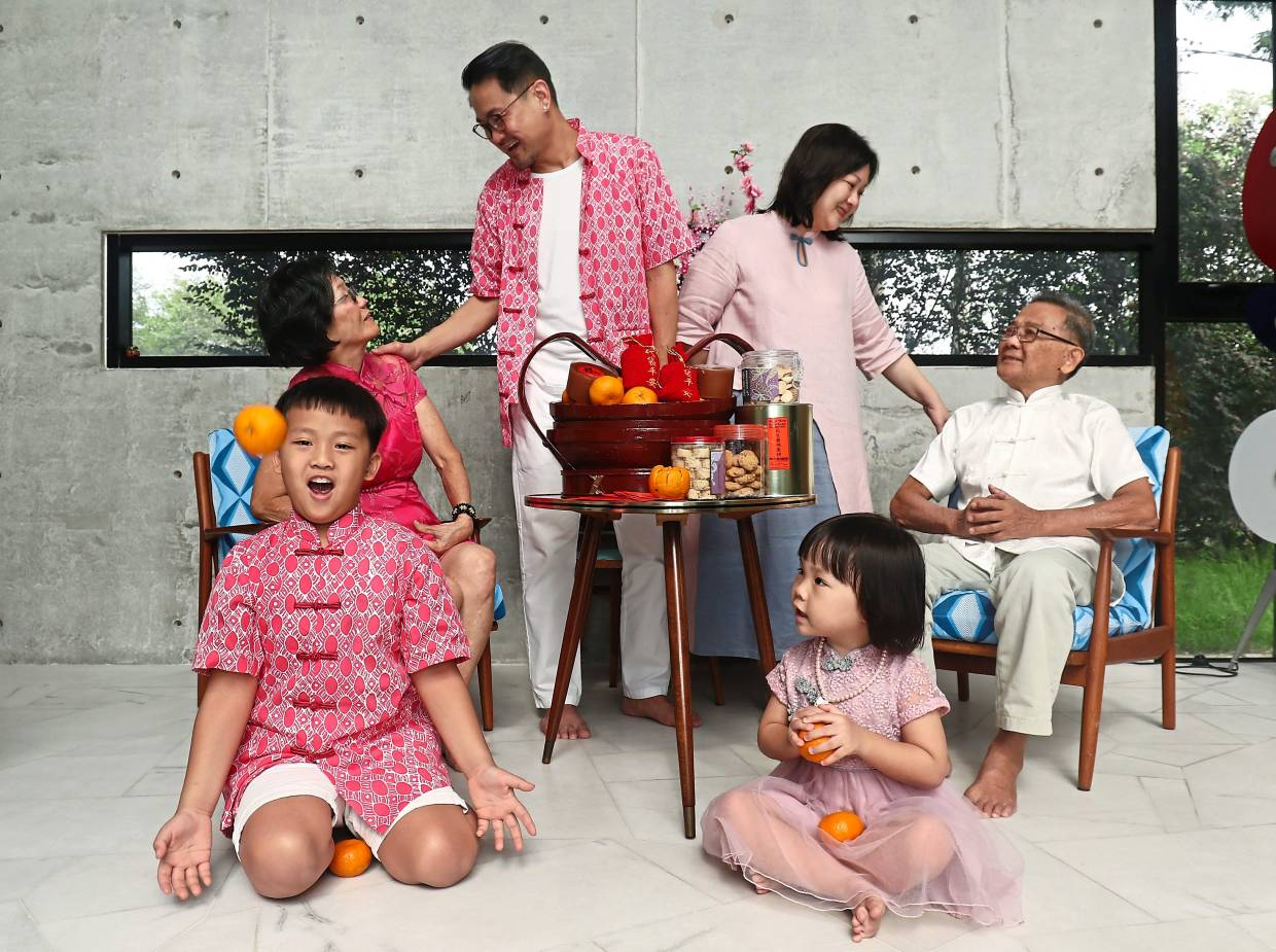 (Clockwise, seated from left) Chew How, 71, Wong, Angeline, 42, Wong Yew Chee, 77, Aliya and Aiden sharing a light moment at their home. — Photos: SAMUEL ONG and FAIHAN GHANI/The Star