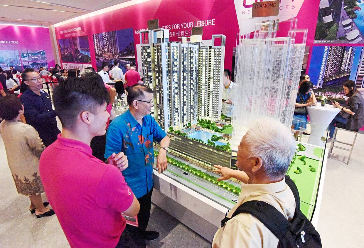 Guests having a closer look at a scale model of the GEM condominium on display after the ground-breaking ceremony at Jalan Baru in Prai.