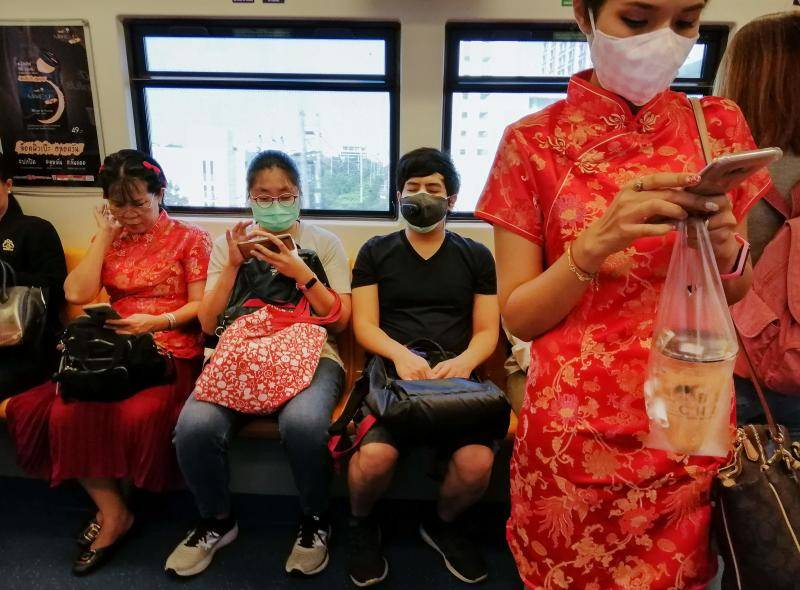 A woman with a face mask wearing a cheongsam ahead of the Chinese Lunar New Year in a train in Bangkok on Friday (Jan 24) after four people were detected with the Coronavirus in Thailand. - Reuters