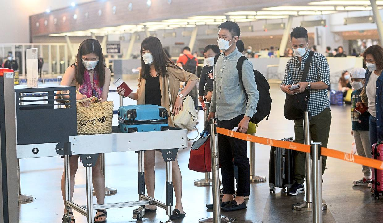 Precautionary measure: Passengers wearing mask as they scan their luggage at the departure terminal in KLIA 2, Sepang.