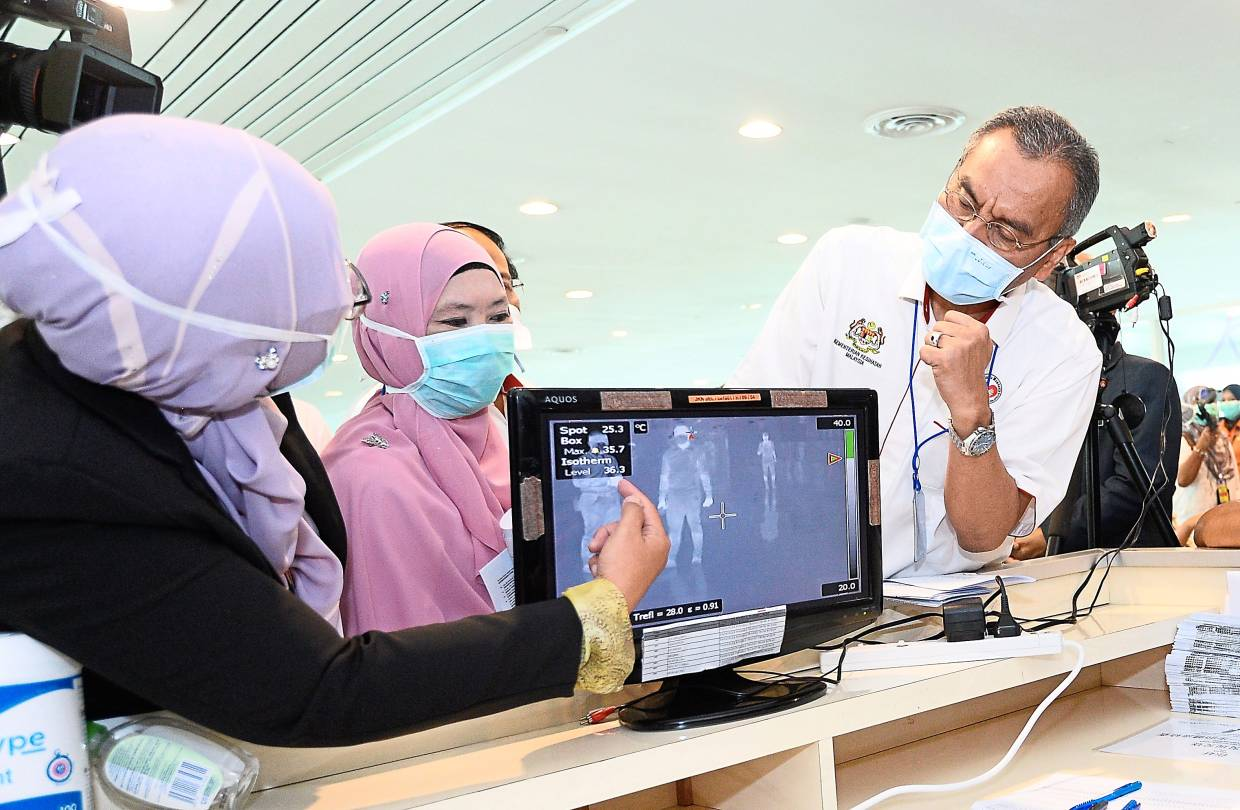 Eye on the situation: Dzulkefly (right) checking on a thermal scanner for passengers as he visits KLIA in Sepang.