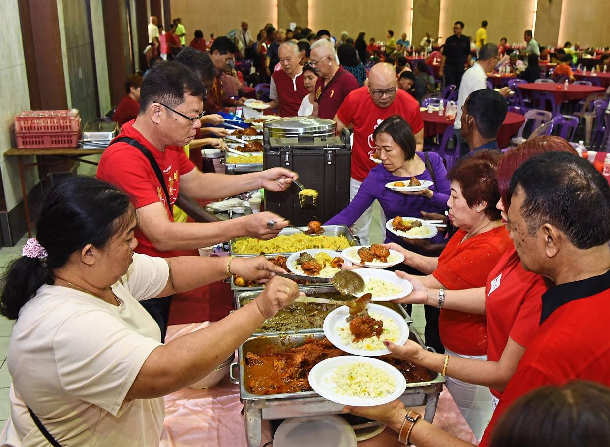 Guests helping themselves to the buffet during the Bukit Bendera constituency open house.