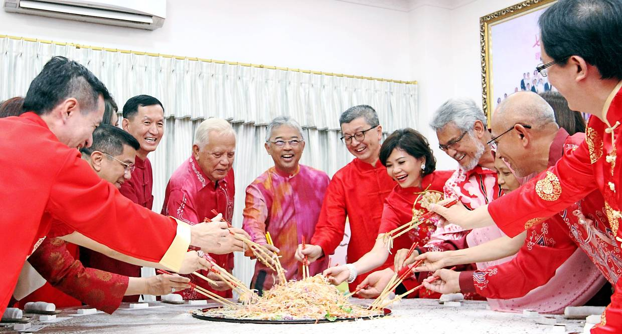 Prosperity toss: The Yang di-Pertuan Agong tossing yee sang with Hock San (on the king's left) with other dignitaries and LBS staff at the recent  LBS Chinese New Year open house celebration.
