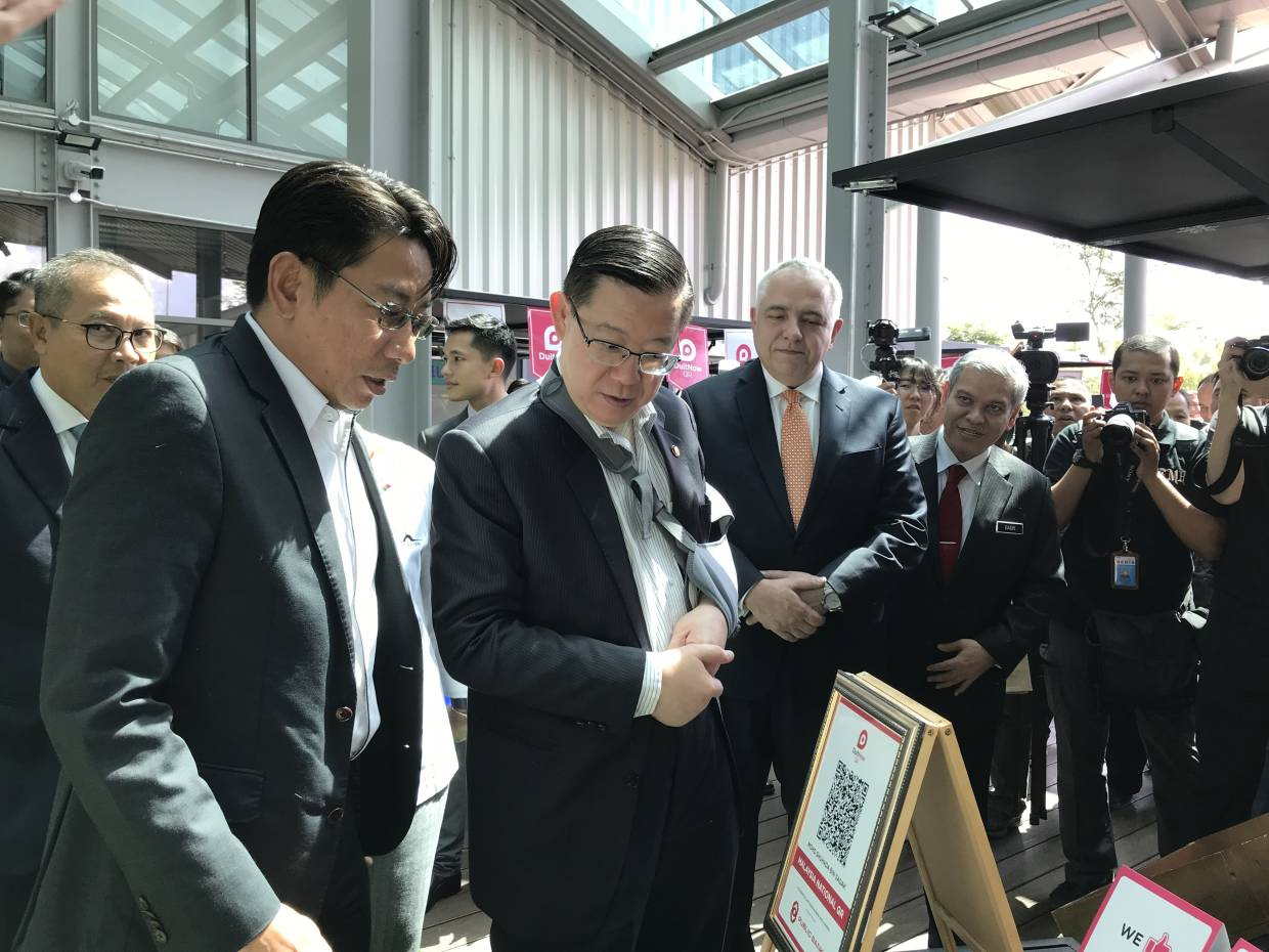 From left: Mohd Najib, Lim, Schiesser, and Cyberview chairman Tan Sri Ahmad Badri Mohd Zahir announcing that the DuitNow QR code will be used citywide in Cyberjaya.