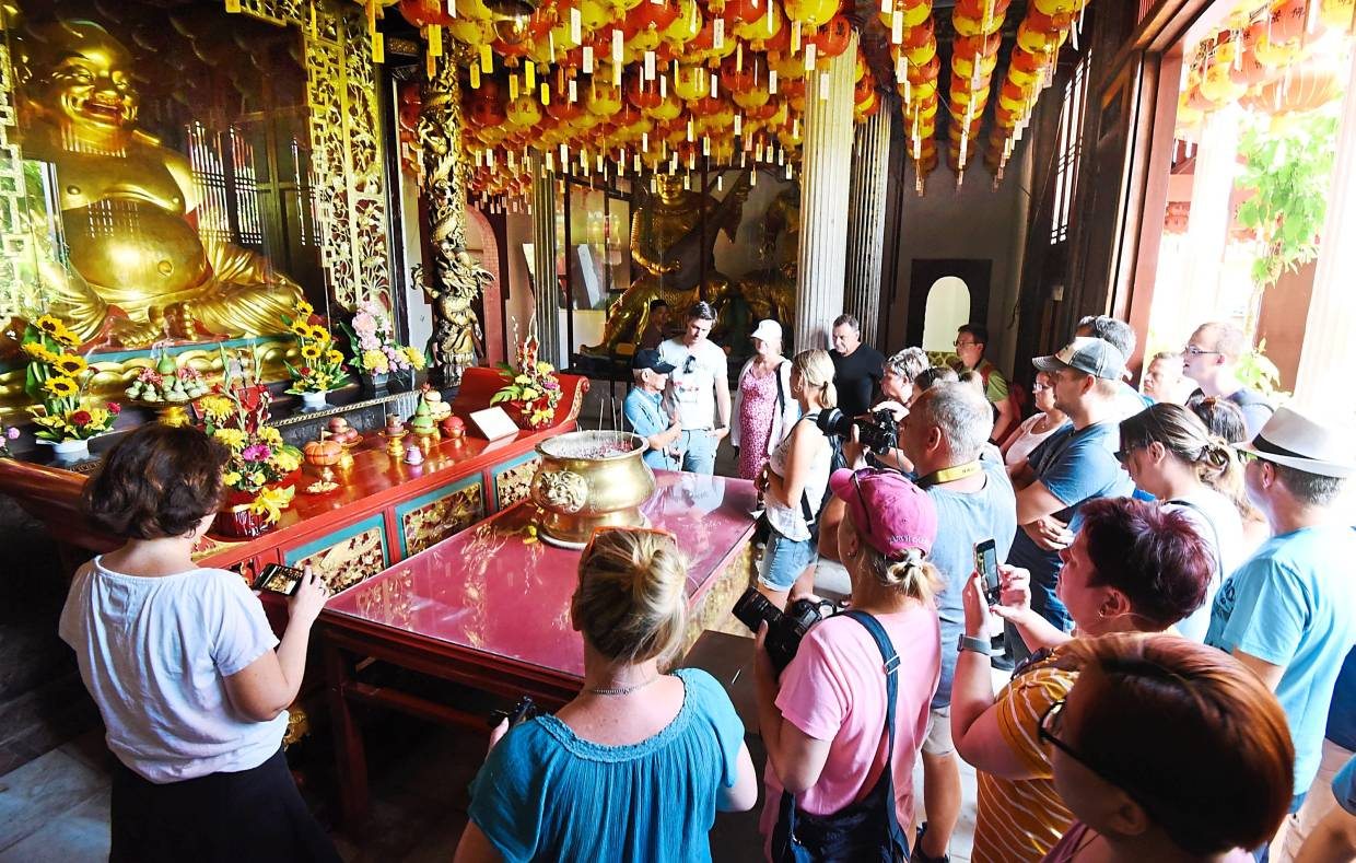 The state government says tourist spots in Penang remain open as usual. Seen here is a group of foreign visitors at Kek Lok Si Temple during this Chinese New Year.