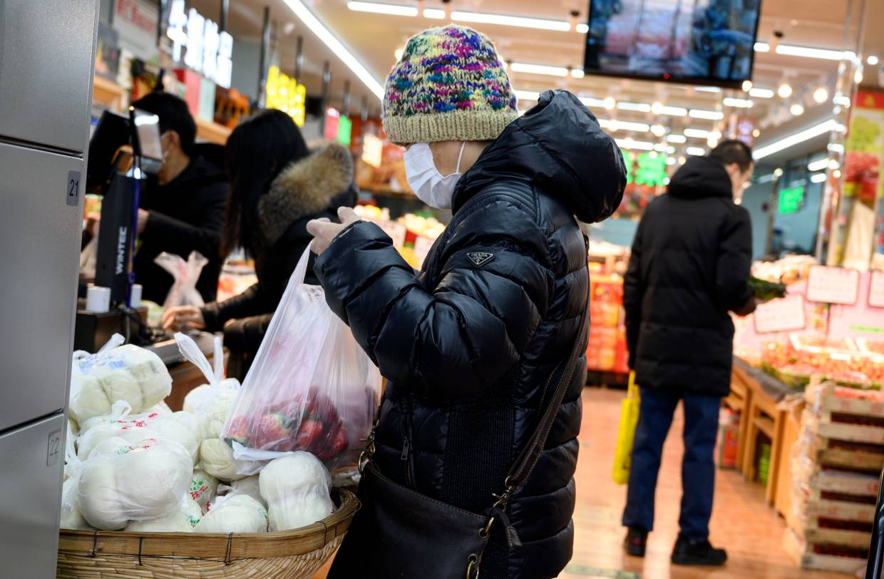 People wearing face masks as they shop in Beijing. — AFP