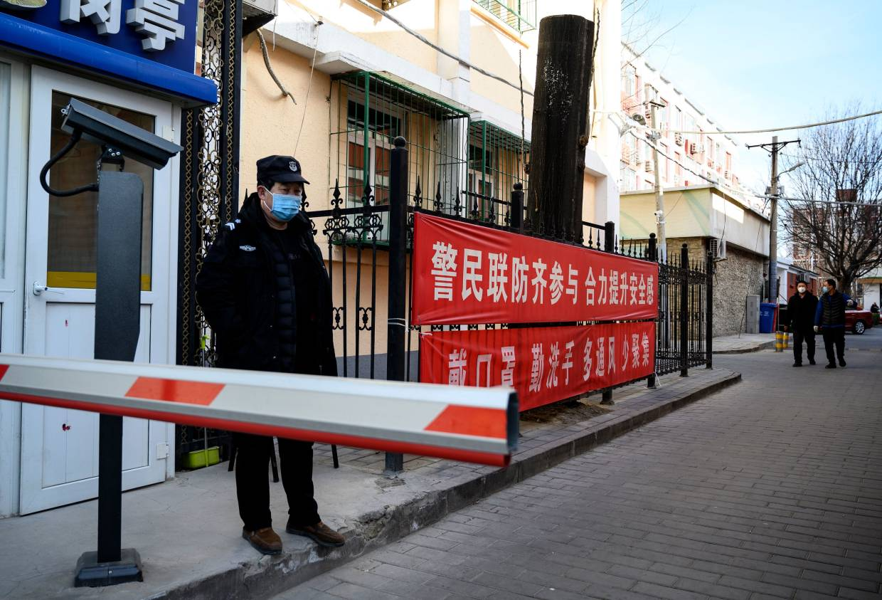 A security guard wearing a protective face mask at a compound with a banner reminding people to wear masks and wash hands in Beijing. — AFP