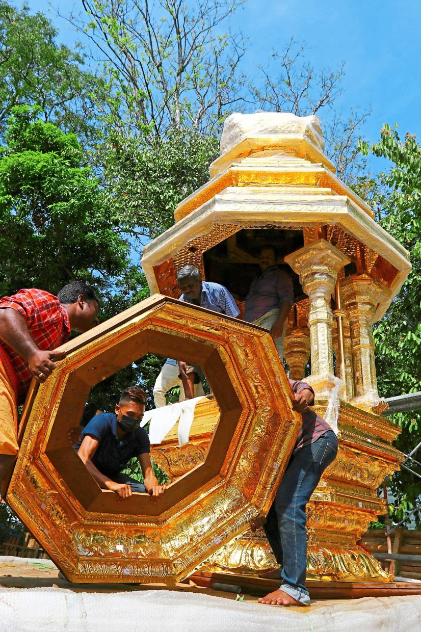 Finishing touches: Workers completing the decoration on the new golden chariot for Thaipusam in George Town.