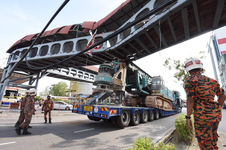 A trailer carrying the piling crane hit an overhead pedestrian bridge near the Pengkalan Raja Tun Uda ferry terminal in Weld Quay, Penang. The bridge was built in the 1970s.  MUSTAFA AHMAD / The Star