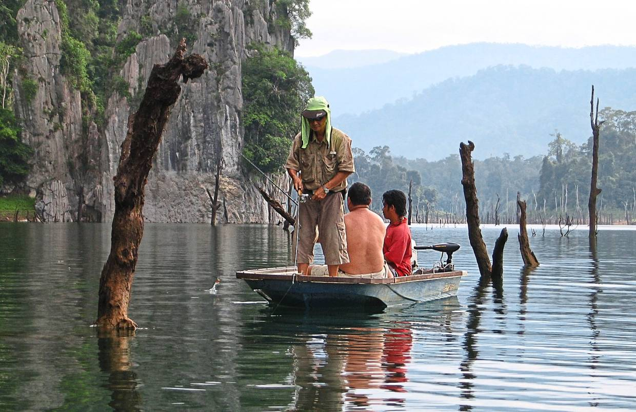 Anglers fishing for 'toman' near the submerged limestone hill in Kenyir dam.