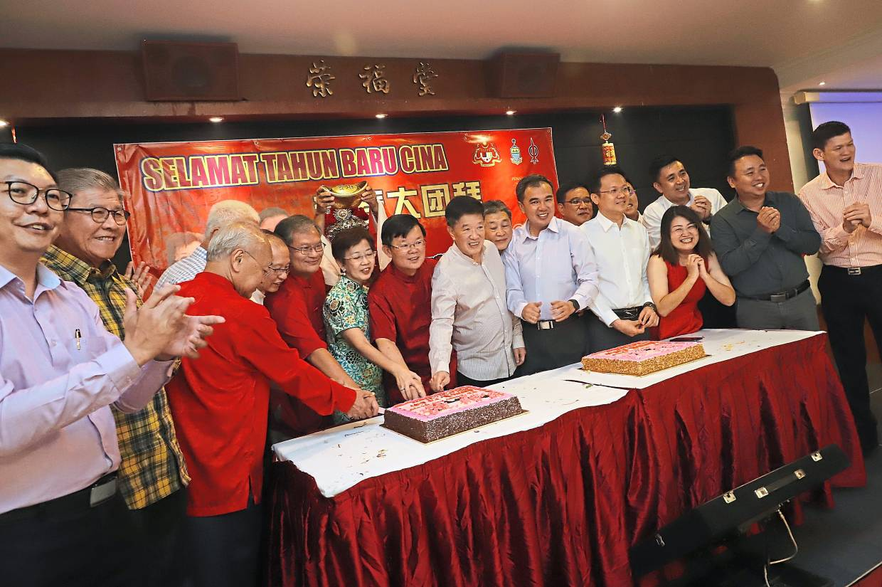 Chow (centre, in red) cutting a cake with guests.