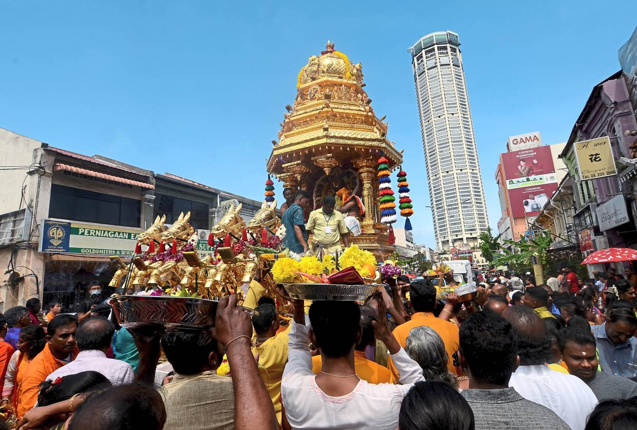 Offerings from devotees: A crowd surrounding the golden chariot as it makes it way down Jalan Datuk Keramat in George Town, Penang on Thaipusam eve. Many in the crowd were seen carrying trays of fruits and flowers as offerings. — (Below) Staff from Sunway Hotel Georgetown and Sunway Hotel Seberang Jaya giving out free food for those walking with the chariots. -  Bernama/The Star