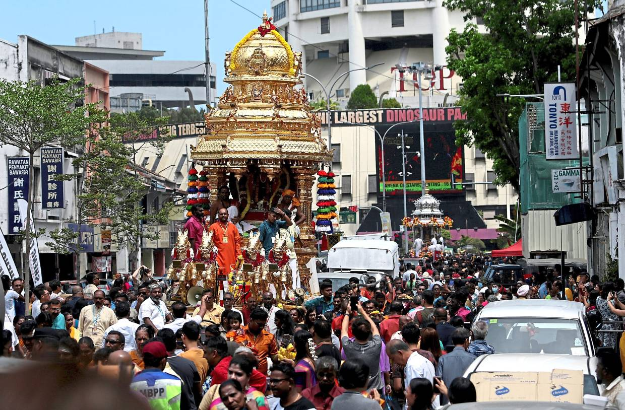 The golden chariot swarmed by devotees during the procession