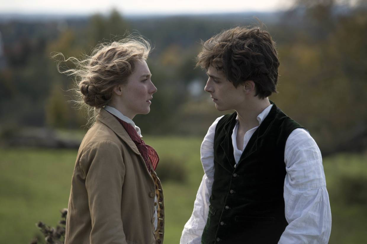 Jo March (Saoirse Ronan) and Laurie (Timothee Chalamet) compare who can rock an old fashioned coat better.
