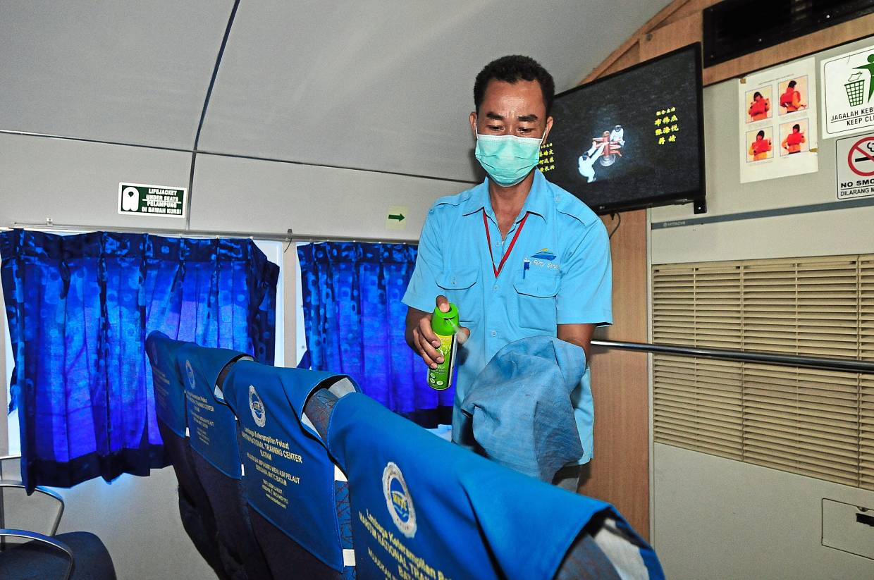 A worker disinfecting the seats on a ferry from Kukup to Tanjung Balai, Indonesia to safeguard passengers against novel coronavirus.