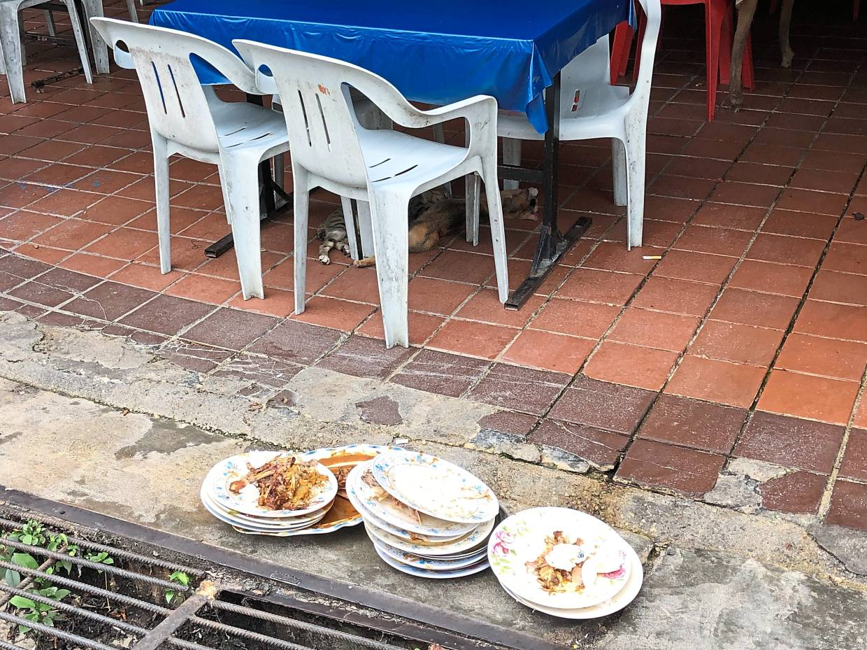 Dirty plates piled up on the floor of the stalls.