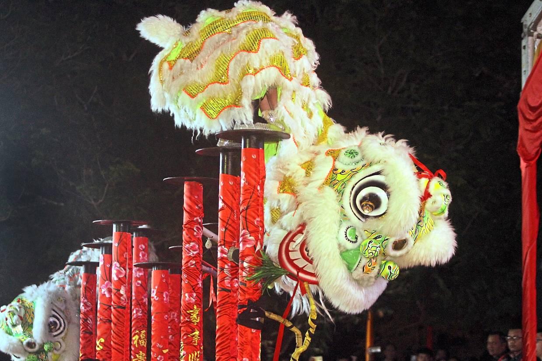 An acrobatic lion dance performance on stilts entertaining the crowd.