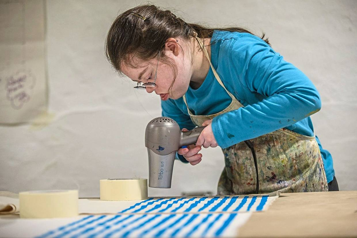 Quiet and not very verbal, Julia Tyler throws herself into creating beautiful items. Here, she uses a hair dryer to dry the paint on her silk-screened placemats.