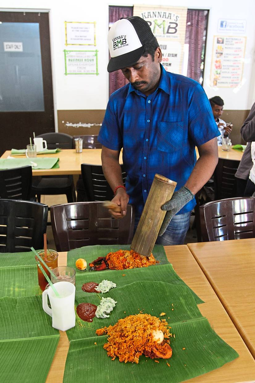 A waiter  tapping the bamboo to shake the  briyani onto the banana leaf. — Photos: LOW BOON TAT/The Star